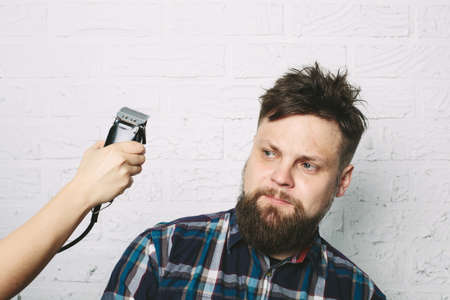 Funny hipster man with beard in hair salon. hairdresser hand with electric razor