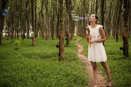 Beautiful woman blowing bubbles in forest Фото со стока