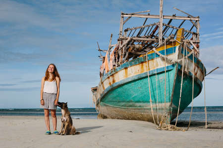 Happy young girl with dog staying on sea beach near old big boat ship and enjoy summer and sea Фото со стока