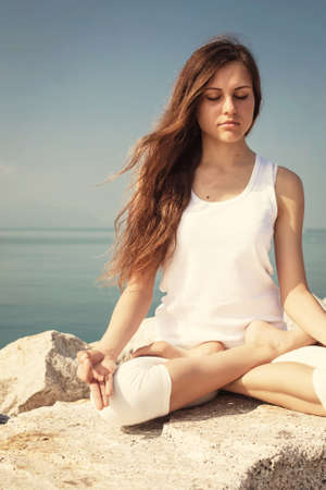 Beautiful young woman relax and meditate in Lotus yoga posture on the beach
