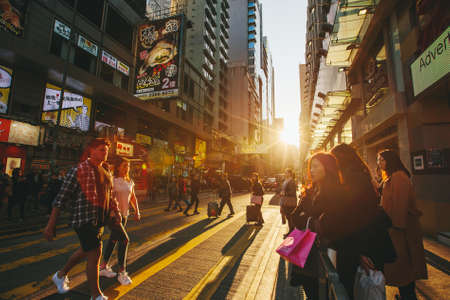 People walking on sunny street on sunrise in Hong Kong