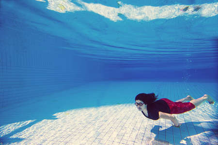 Asian young woman in business clothes and glasses  under water