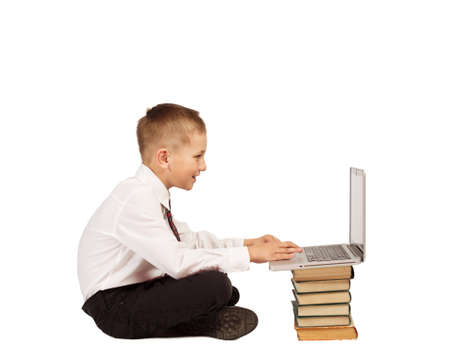 Little Boy sitting and typing on laptop computer and books. Home school, technology education. White background isolated