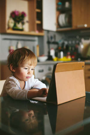 Little baby Girl sitting on kitchen with tablet pc using touchscreen