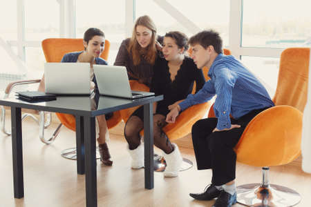 Group of young colleagues using laptop computers at office. Team discuss