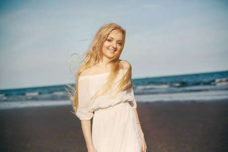 Smiling happy Blond woman in white dress enjoy vacation outdoor on sea beach. Sunny summer day, happiness Фото со стока