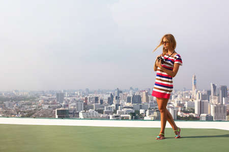 Beautiful woman photographer on the roof of a skyscraper in travel