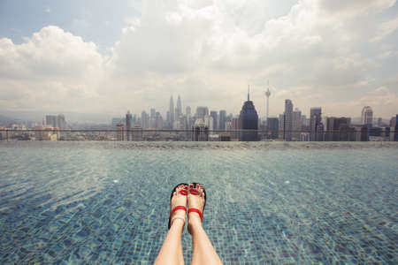 Vacation in Kuala-Lumpur. Young woman photographing her feet in sandals while swimming in roof top pool with beautiful city view Фото со стока