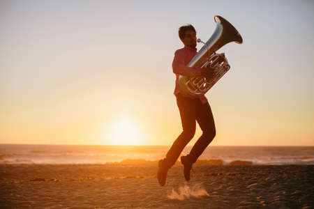 Silhouette of young man playing and jumping with Tuba on rocky ocean coast during sunset. Music outdoor Фото со стока