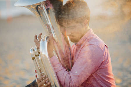 Young man with Tuba musical instrument  on sea shore  outdoor