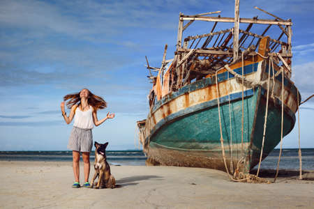 Beautiful happy young girl with dog staying on sea beach near old big boat ship and enjoy summer and ocean wind Фото со стока