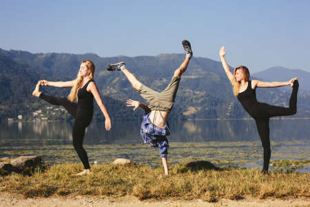 Happy funny yoga people try to doing fitness yoga exercises outdoor on beautiful mountain lake in Nepal