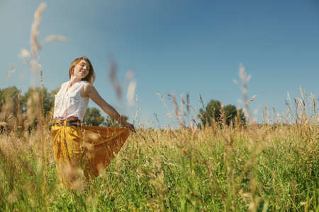 Free Happy Woman Enjoying Nature. Beauty Girl Outdoor. Freedom concept. Beauty Girl over Sky and Meadow
