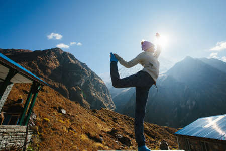 Young sport woman doing fitness exercise in tourist trekking on Himalaya mountains sunrise background Фото со стока