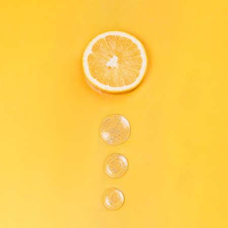 Orange slice and round drops on an orange background medical concept