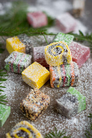 Christmas sweets on a wooden background decorated Christmas tree. Ideas for Christmas and the New Year. Colored candy. Ideas for kids at Christmas. Turkish sweets for tea and coffee. Turkish Delight. Imagens