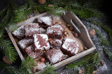 Christmas card. Christmas tree on a black wooden background with sweets and biscuits. The original idea of ??Christmas. Chocolate cake. Brownie With tree of powdered sugar. New Year Imagens