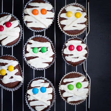 Funny idea for Halloween dessert - cute mummy cupcakes on a black wood background top view blank space for text Halloween. childrens holiday. Chocolate cupcakes colored eyes. Food for Halloween.