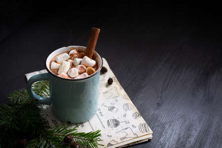 Hot chocolate with marshmallows on the wooden black background with kraft paper. Christmas tree with style.Hot cocoa with marshmallows.New Year.Christmas.Holiday card.Rustic style.Cinnamon.Copy Space Imagens