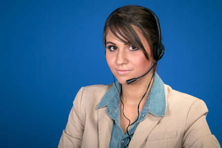 Young woman with headset against blue backgroun photo