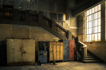 Abandoned industrial interior with cupboard and stair photo