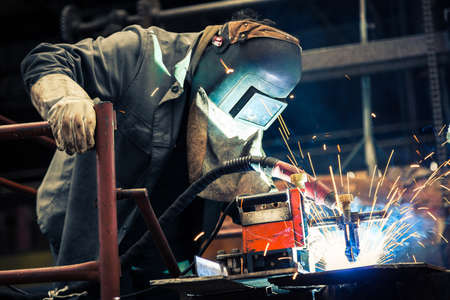 heavy industry: Industrial Worker at the factory welding closeup