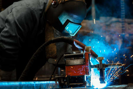 skilled labour: Industrial Worker at the factory welding closeup