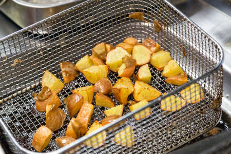 deep fryer with fried potato closeup