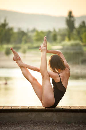 Young woman is practicing yoga in nature
