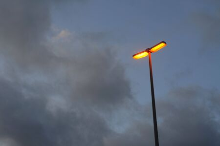 Orange glowing streetlamp under a stormy, cloudy sky