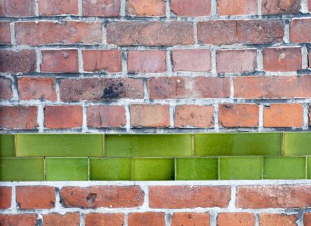 Old red brick wall with row of green enamel tiles, architectural background