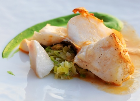 foaming: Fried codfish with leek brunoise, green vegetable cream and foaming sauce, gourmet dish