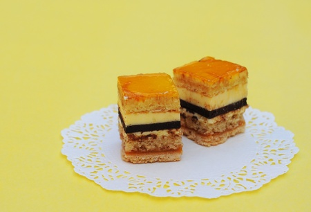 Fine fruit cakes, on lace paper, on yellow background, shallow dof Stock Photo
