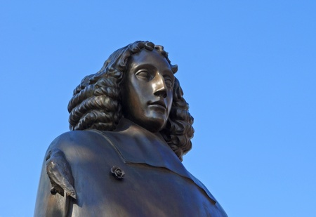 Statue of Spinoza in Amsterdam against blue sky