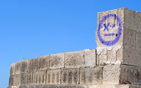 Purple simple graffiti on rough grey volcanic brick building against blue sky, room for text Stock Photo