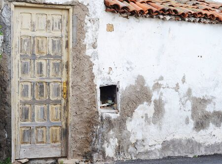 Old wooden door with brass doorhandle and rough wall with open water meter, Tenerife, copy space photo