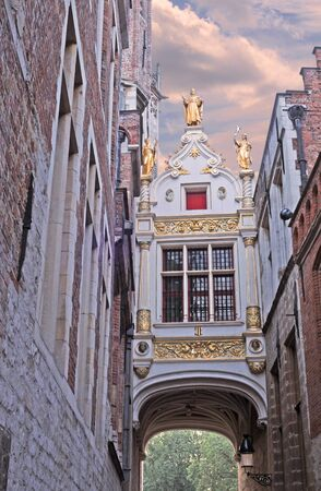 Bruges, Blinde Ezelstraat, small passage with beautiful renovated building and golden statues Stock Photo - 12358581