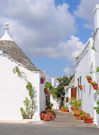 trulli: Trulli houses with conical roofs and lots of flowerpots in Alberobello, Italy, Europe