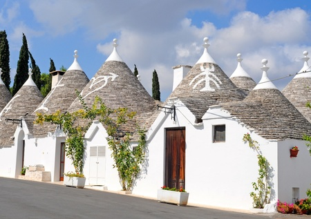 Trulli houses with painted symbols on the conical roofs in Alberobello, Italy, Puglia