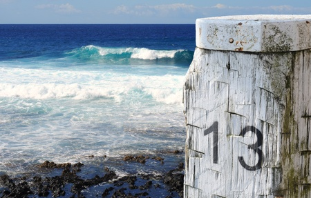 Mooring post or bollard 13 in front of deep blue ocean and waves photo