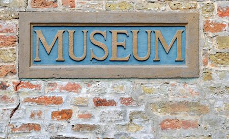 Museum vintage sign in blue an gold painted against brick wall