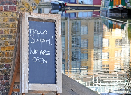 noteboard: Wooden blackboard by the waterside with text