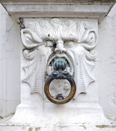nosering: Mythical stone head as a doorknob, detail of old court of justice Brugse Vrije, Bruges