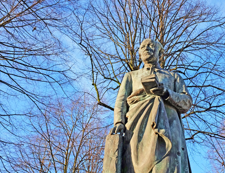 Bronze statue of the Flemish poet en priest Guido Gezelle against winter trees and blue sky background, Bruges, Belgium, Europe Stock Photo