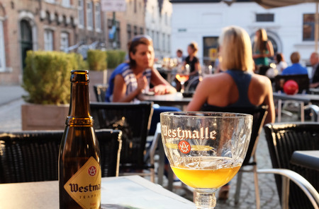 BRUGES, BELGIUM - AUGUST 23, 2013: Half a glass of Westmalle, a Belgian beer produced by monks, currently one of the ten authentic trappist products in the world. Selective focus Editorial