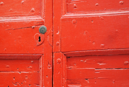 Detail of old wooden red painted door with heart shaped key hole Stock Photo