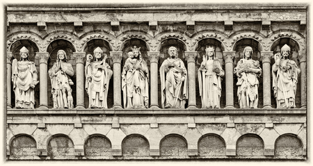 Detail in gable of Our Lady Visitation church, Rochefort, Belgium, Wallonia, antique sculptures of diverse holy persons, monochrome sepia image