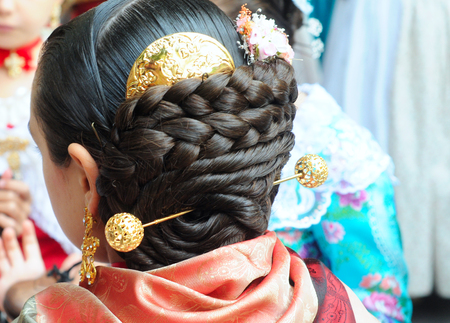 VALENCIA, SPAIN - NOVEMBER 9, 2014: traditional Valencian street party where inhabitants of all ages dance dressed in beautiful, original, handmade clothes and with typical hairstyle