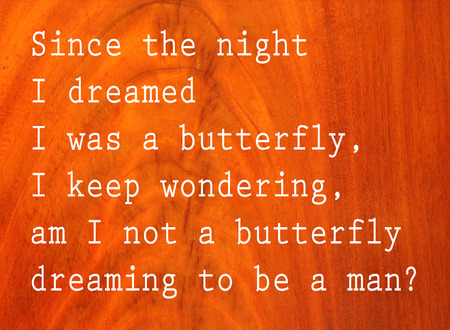 Since the night I dreamed I was a butterfly, I keep wondering, am I not a butterfly dreaming to be a man, text on antique cherry wood background Stock Photo