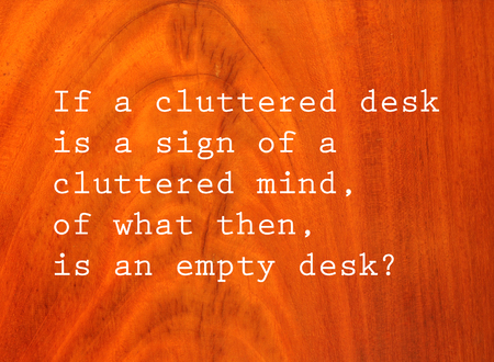 cluttered: If a cluttered desk is a sign of a cluttered mind, of what then is an empty desk? Text on antique cherry wood  background Stock Photo